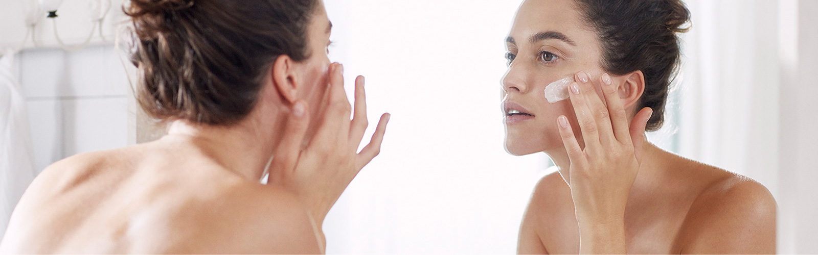 Woman moisturizing her face
